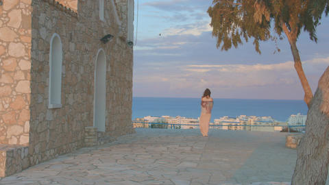 Young lonely woman looking at evening sky above sea. Vacation at seaside resort Footage