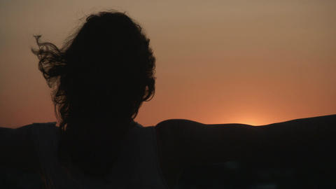Dark silhouette of woman watching sunset, sunrise. Hair waving in wind. Mystery Footage