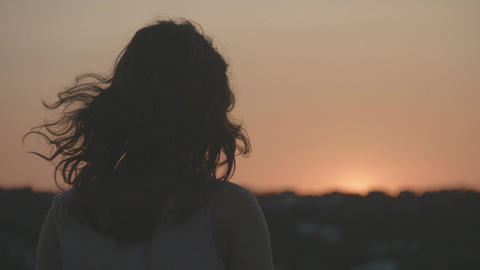 Silhouette of young lonely female watching sunset, sunrise. Beautiful pink sky Footage