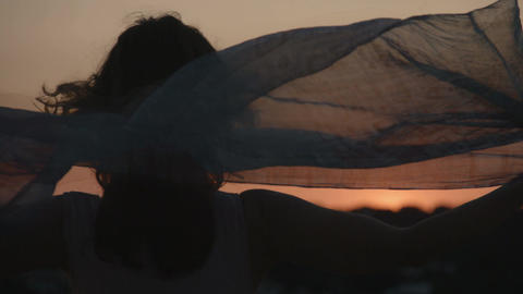 Silhouette of woman holding scarf in the wind, watching sunset, sunrise. Freedom Footage