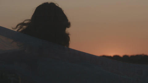 Female silhouette enjoying view of pink sky at sunset, holding scarf in the wind Footage