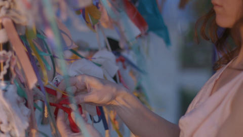 Closeup of woman tying a ribbon to the wishing tree. Traditions, symbol of luck Live Action