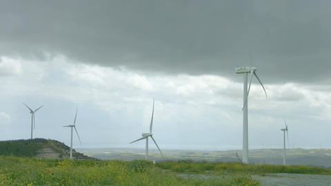 Wind turbines spinning in green field under gray stormy sky, bad rainy weather Footage