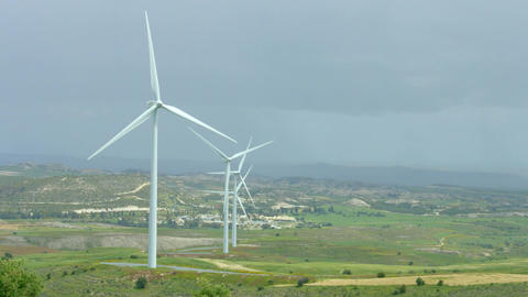 Beautiful landscape with green hills and rotating wind turbines, green energy Footage