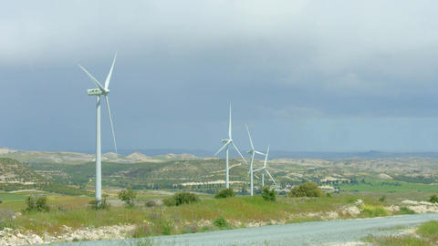 Renewable energy source, modern windmills spinning, green field, stormy horizon Footage
