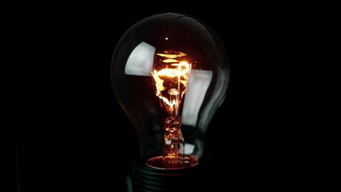 turn on and turn off, retro vintage light bulb with tungsten technology built-in on black Live Action