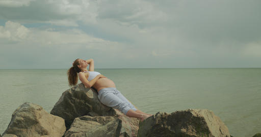 Beautiful pregnant woman on a sea bank, Young woman waiting for her baby Live Action