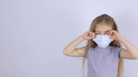 Child in a protective medical mask rubs his eyes with his hands Live Action