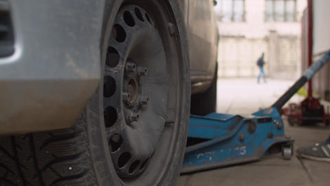 Mechanic in a vehicle workshop lifting a car on a jack Live Action
