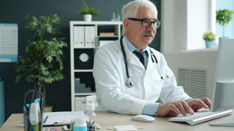 Medical specialist in uniform working with computer typing in clinic office Live Action