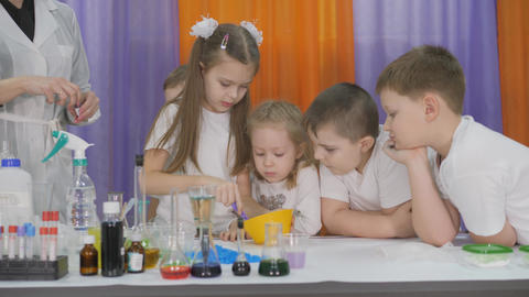 Chemical experiments for children. Children add ingredients to a yellow bowl and stir. Room is Live Action
