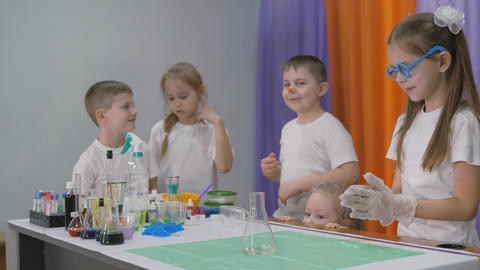 Chemical experiments for children. Girl pours ingredients into a transparent dish. Bright emotions Live Action