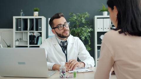 Young man doctor is consulting unhealthy female patient in clinic office talking Live Action