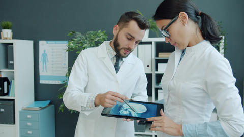 Man and woman medics using tablet looking at x-ray image working in office Live Action