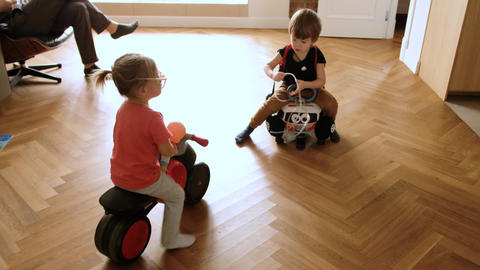 Sibling riding toy vehicles at home Live Action