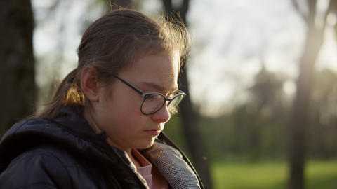 Closeup pretty girl sitting in sunny park. Teenager girl reading outdoors Live Action