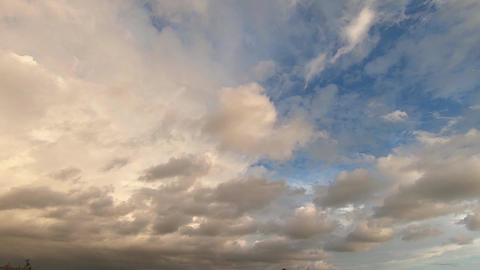 Time-lapse of a dramatic cloudy sky with clouds quickly covering the sun on the blue sky at sunset Live Action
