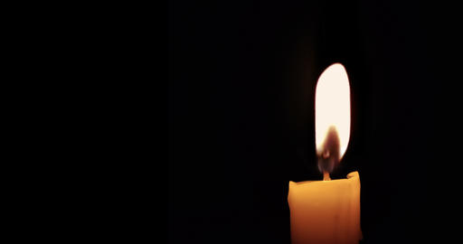 close-up of candle burn with glow flame fire sparkle on black background, with copy space for text, Live Action