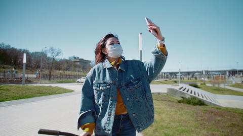 Young asian woman blogger in a jeans jacket and medical mask walks with the Live Action