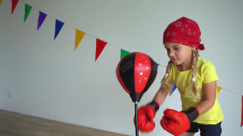 Strong active girl boxing pear with boxing gloves. Child training at sports club Live Action