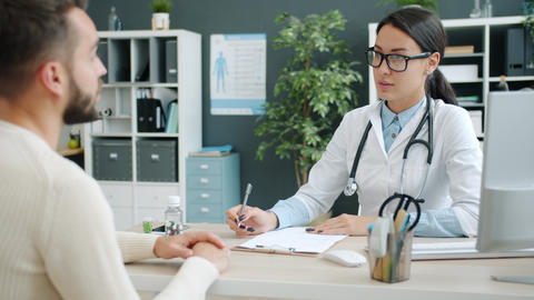 Female medic consulting unhealthy man in hospital office talking writing in Live Action