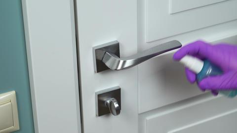 Sanitizer disinfection of handle on door in room Live Action