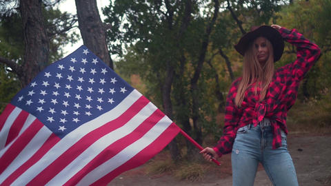 Girl in a cowboy hat with an American flag. The concept of patriotism. USA Live Action
