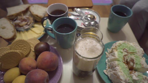 Table setting for tea drinking, various goodies and drinks. Close-up with a Live Action