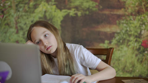 Bored girl comparing information in laptop and textbook Live Action