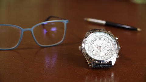 Close up view of wrist watch and eyeglasses on table GIF