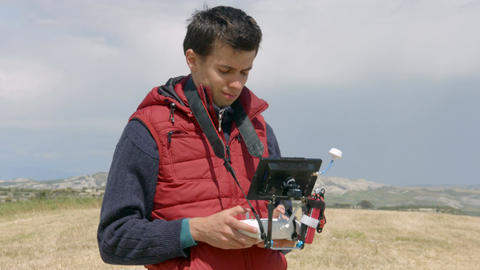 Professional cameraman controlling drone flight, watching display, filming video Footage