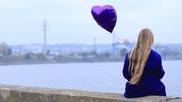 Sad girl with broken heart holding heart balloon Footage
