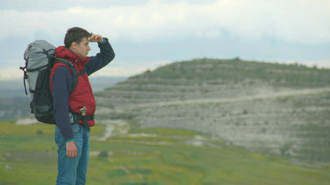 Guy on top of mountain or hill looking at green valley, enjoying natural beauty Footage