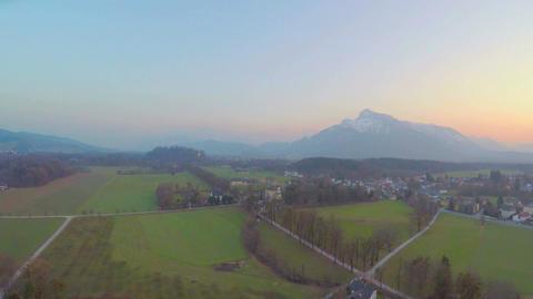 Panorama of green fields in rural area, rocky mountain on horizon, Austrian Alps Footage