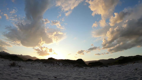 Time lapse of sunset sky with clouds that hide the sun coming out and illuminating the sand dunes ライブ動画