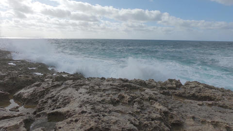 Slow motion of the stormy sea with the waves crashing on the limestone rocks with high water ライブ動画