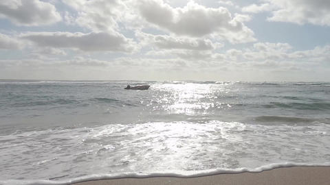 Slow motion of an isolated boat on the sea waves crashing on the shore with the sun reflections in Live Action