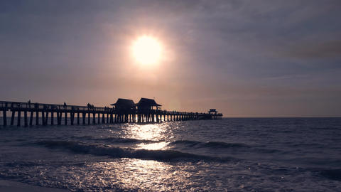 Dark silhouette of a pier over the ocean at sunset Live Action