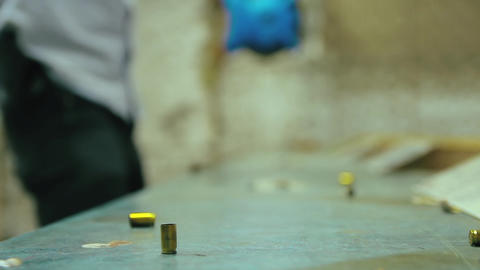 Cinemagraph of empty pistol bullet shell dropping and impacting wooden table in a shooting range Live Action