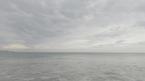 Suggestive slow motion of the sea almost flat with the cloudy gray sky in flat color Live Action