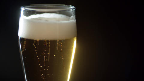 Full glass of beer with foam and gas bubbles Live Action