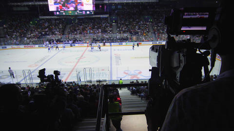 silhouette of cameraman filming interesting hockey game Live Action