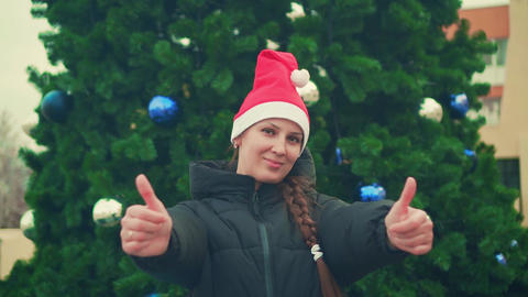 Young woman in santa hat on christmas tree background. Happy pretty woman Live Action