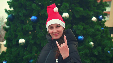 woman in santa hat showing like sign, rock sign, communication concept Live Action