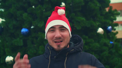 Young man with beard in santa hat on christmas tree background. A happy man Live Action