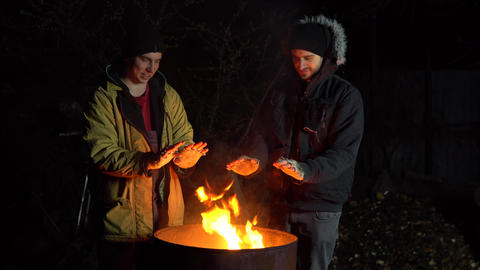 Two homeless young men bask in the fire. Men stand near a barrel of fire at Live Action