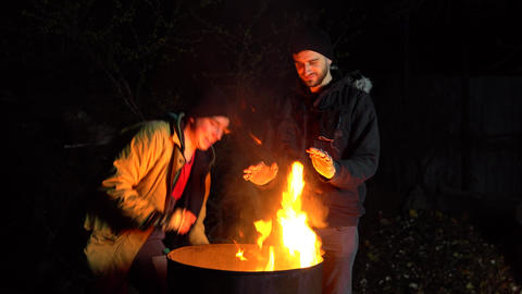 Two homeless young men eat apples. Men stand at night near a barrel of fire and Live Action