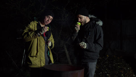 Two homeless young men are frying apples on a fire. Men stand at night near a Live Action