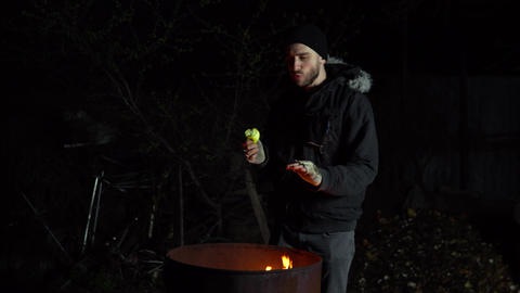 A homeless young man stands by the fire and eats an apple. A man stands at night Live Action