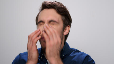 Sick man sneezing on light background. Student sneezing from allergy Live Action
